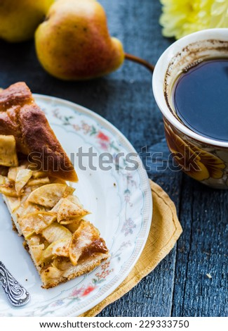 apple pie with a cup of coffee, breakfast on a dark board and window