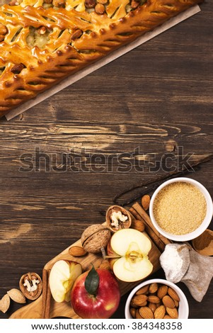 Apple pie with almonds and cinnamon and ingredients over brown wooden table - stock photo