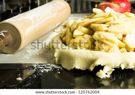Apple pie with apples filling and rolling pin - stock photo