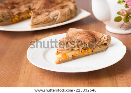Apple pie with common sea-buckthorn and cinnamon on wooden background - stock photo
