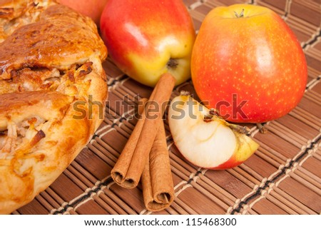 Apple pie with fresh apples and cinnamon sticks