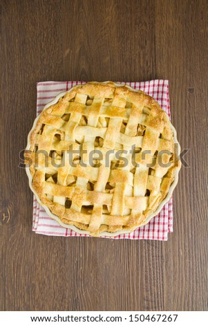 Apple pie with lattice top on red gingham