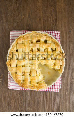 Apple pie with lattice top with slice removed - stock photo
