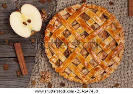 Apple pie with raisins, nuts and cinnamon on vintage wooden background texture. Top view - stock photo