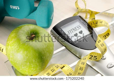 apple, scale and dumbbells for a healthy life and fitness message
