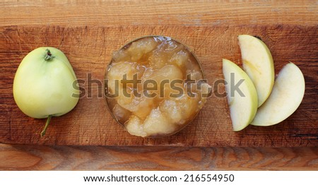 Apple, slices and jam on brown cutting board, viewed from above in daylight. Focus on jam.  - stock photo