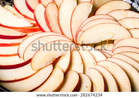 Apple slices arranged in skillet to make apple cake - stock photo