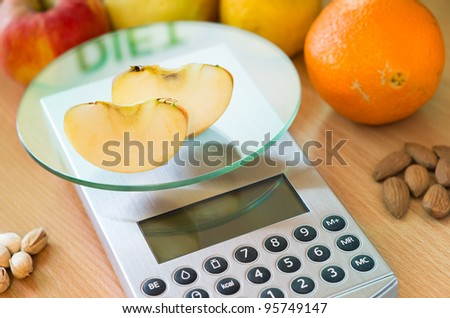 apple slices on digital kitchen scale and word diet reflected - stock photo