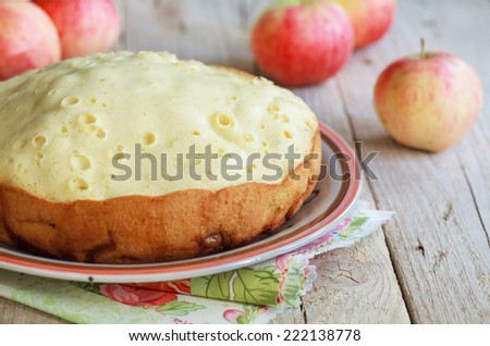Apple sponge cake cooked in multicooker on a wooden table, selective focus