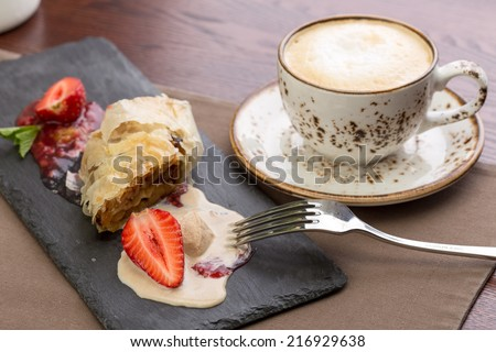 Apple strudel cake served with cappuccino coffee on the table at restaurant - stock photo