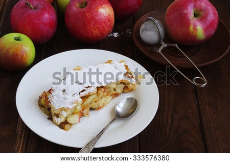 Apple Strudel dusted with  icing sugar on a white round plate with a silver spoon