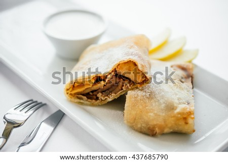 Apple strudel served on white plate - stock photo