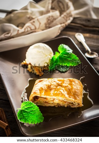 Apple strudel with ice-cream decorated by mint on ceramic plate. Selective focus. - stock photo