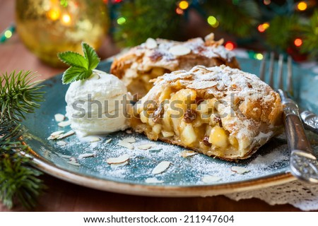 Apple strudel with icing sugar,almonds and vanilla ice cream for Christmas - stock photo