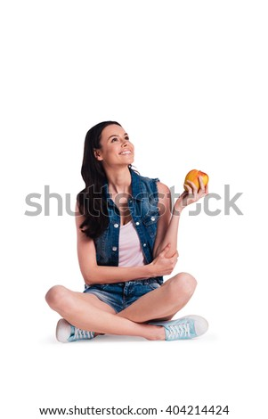 Apple time! Beautiful young cheerful woman holding apple and looking up with smile while sitting in lotus position against white background - stock photo