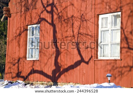 apple tree shadow on winter farm house red wooden wall - stock photo
