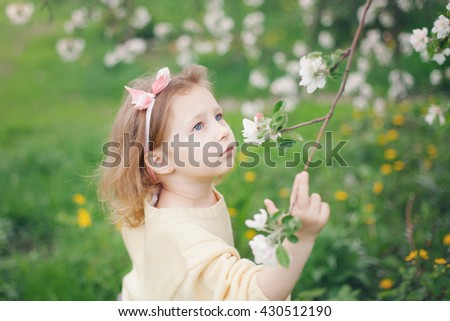 Apple trees in bloom. Beautiful little girl enjoying the aroma of apple blossom - stock photo