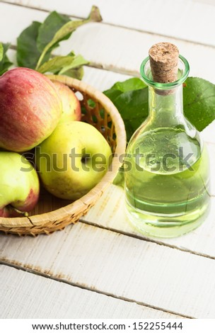 Apple vinegar and apples on white wooden table. Selective focus.