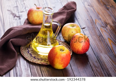 Apple vinegar and apples on  wooden table. Selective focus, horizontal. - stock photo