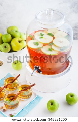 Apple, white wine punch, tea, mulled cider with spices in a beverage dispenser with fresh apples and mint leaves - stock photo