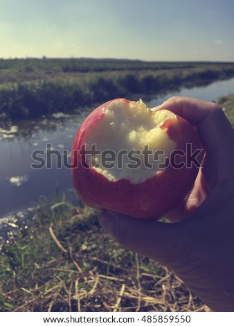 Apple with bite in hand against a rural background