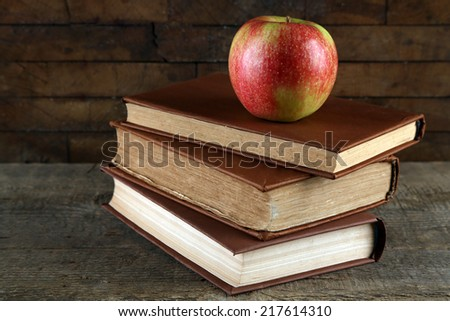 Apple with book on wooden background - stock photo