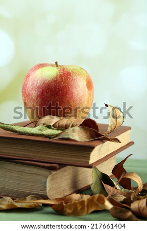 Apple with books and dry leaves on table on bright background - stock photo