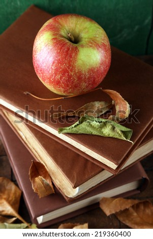 Apple with books and dry leaves on wooden background - stock photo