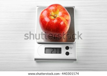 Apple with digital kitchen scales on wooden background - stock photo