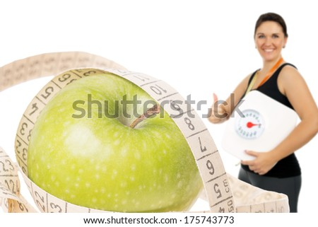 Apple with measuring tape and woman with the body scale / healthy eating