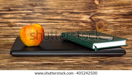 Apple with notepad on closed laptop - stock photo