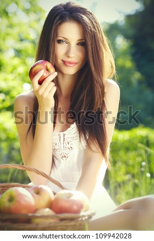 Apple woman. Very beautiful ethnic model eating red apple in the park. - stock photo