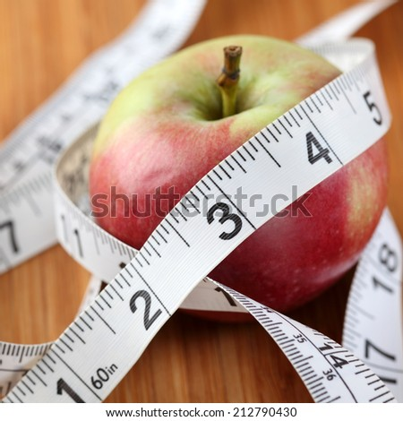 Apple wrapped in a tape measure. Diet concept. Shallow depth of field. Close-up.