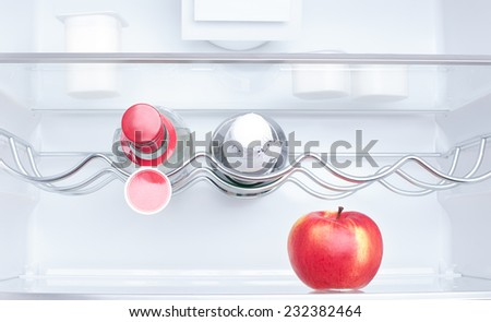 apple, yogurt and two bottles in a refrigerator - stock photo