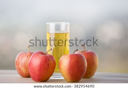 apples and apple juice on a wooden table, outdoor - stock photo
