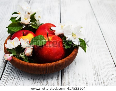 apples and apple tree blossoms on a wooden background - stock photo