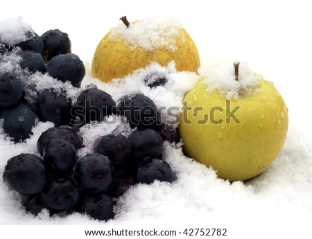 apples and grapes on snow in winter garden - stock photo