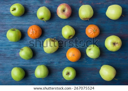 Apples and oranges on old wooden background - stock photo