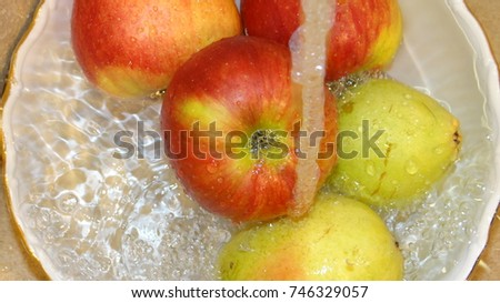 Apples and pears in the jets of pure water in a porcelain dish.