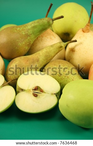 Apples and pears on a green background.