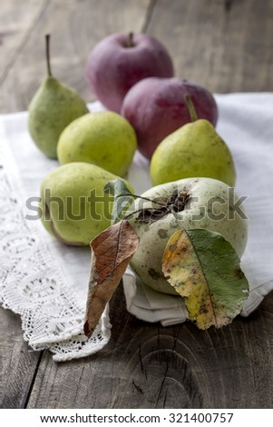Apples and pears on the rustic wooden background