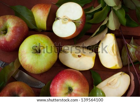 Apples and tree branch with green leaves - garden or orchard harvest. Rustic style image.