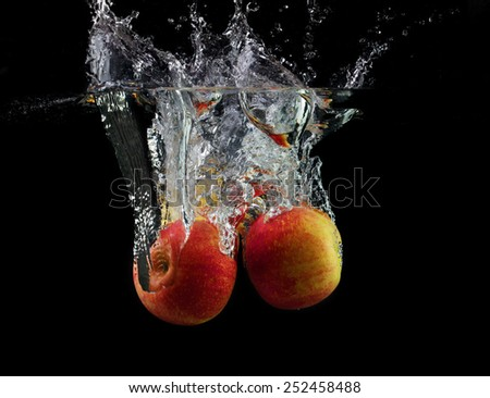Apples are falling into the water with a splash on a black background. Wash fruits. - stock photo