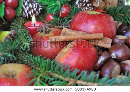 apples, cinnamon, and chestnuts in christmas decoration