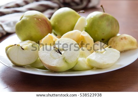 Apples cut on a white plate on wooden table