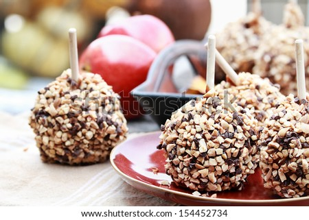 Apples dipped in caramel, chocolate chips and nuts with selective focus on center apple with extreme shallow depth of field. - stock photo