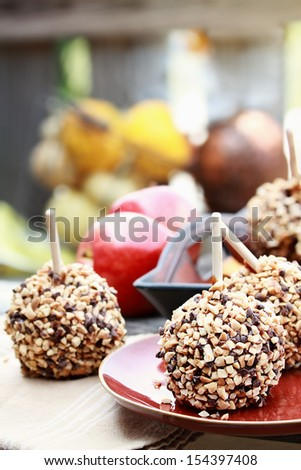 Apples dipped in caramel, chocolate chips and nuts with shallow depth of field. - stock photo