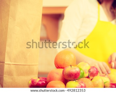 Apples hobby diet salad concept. Female cook working in kitchen. Young lady in apron preparing healthy food out of natural fruits.