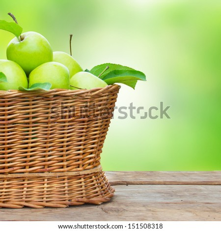 apples in a basket on wooden table against garden background - stock photo
