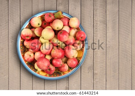 apples in a bowl on wooden background - stock photo
